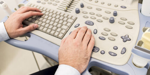 Doctor working on ultrasounds keyboard